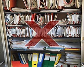 Exemple d'armoire mal organisée : des piles de documents désordonnées, des dossiers suspendus surchargés et même cassés, des classeurs et des boites en désordre